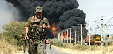 A Georgian soldier walks away from the burning fuel train near Gori (David Mdzinarishvili/Reuters)