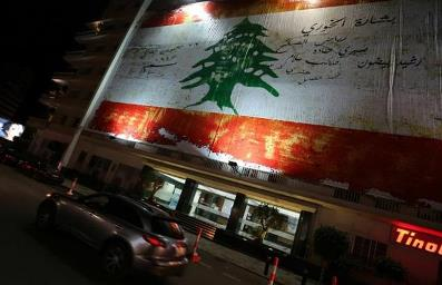 A giant copy of the original Lebanese flag, drawn and approved by the members of the parliament during the declaration of independence in 1943, hangs on the wall of a building in Beirut on the occcasion of Lebanon's Independence Day on November 21, 2014. AFP PHOTO/JOSEPH EID